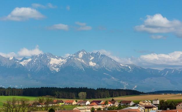 Wiosenny widok na wysokie tatry ze śniegiem na zboczu góry i wiosce (słowacja)
