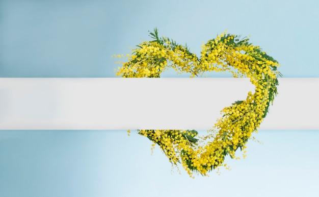 Wiosenny wieniec z kwiatów mimozy w kształcie serca z miejscem na kopię. dzień kobiet, dzień matki, koncepcja karty wiosny