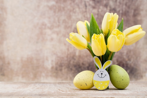 Wiosenny wystrój, żółte tulipany z pisankami.