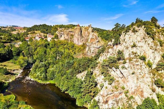Wioska arlempdes z zamkiem na szczycie bazaltowej skały w zakolu rzeki loary. górna loara, francja