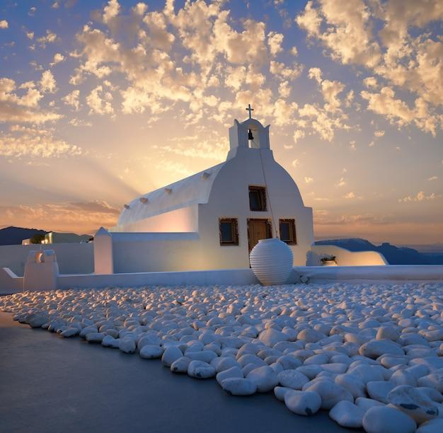 Wioska oia, wyspa santorini w grecji. kaplica na wschodzie słońca z białymi kamieniami