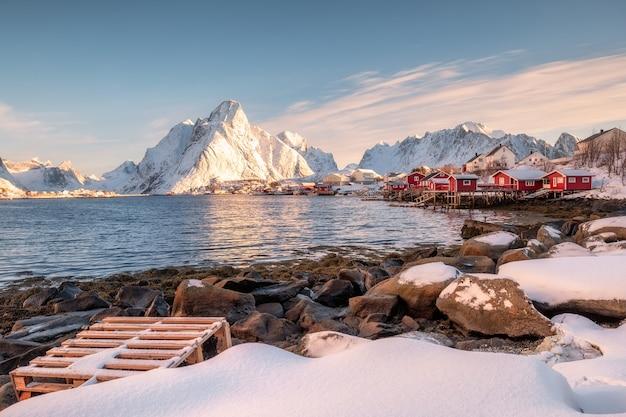 Wioska rybacka na wybrzeżu ze słońcem na górze zimą na lofotach, norwegia