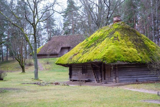 Wioska. stary drewniany dom z bali. widok z oknem, drzwiami przednimi i mchem na dachu.