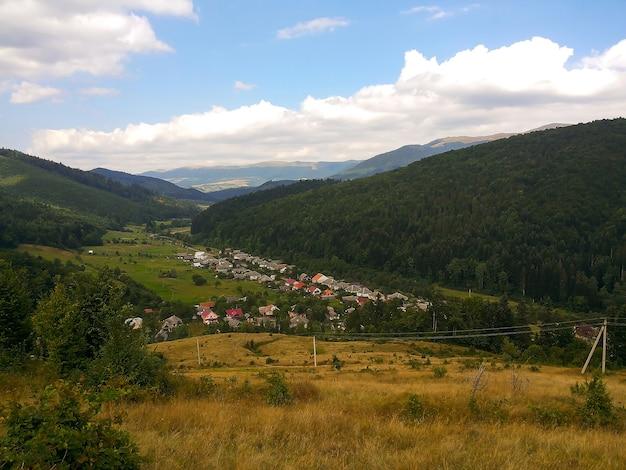 Wioska w dolinie na tle kilku zalesionych gór i błękitnego nieba z chmurami