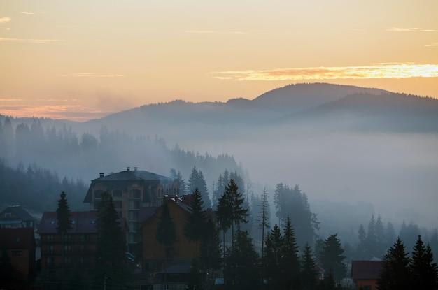Wioska wypoczynkowa mieści budynki na tle mglistych górskich wzgórz pokrytych gęstym mglistym świerkowym lasem pod jasnym różowym niebem o wschodzie słońca. górski krajobraz o świcie.