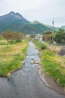 Wioska yufuin, rzeka, góra yufu i błękitne niebo z tłem chmur, yufuin, oita, kyushu, japonia