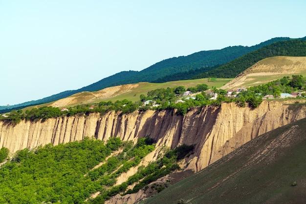 Wioska z domami na skraju zalesionych wzgórz