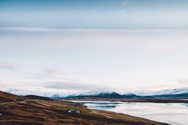 Wioska z gospodarstwami rolnymi w obszar wiejski górach iceland, z śnieżnymi górami w tle.