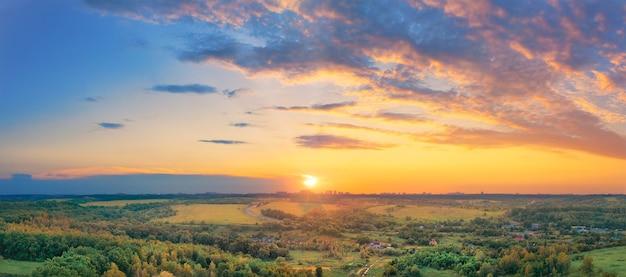 Wioska z małymi domkami pośrodku doliny we mgle o zachodzie słońca z pięknym niebem i żółtym słońcem.