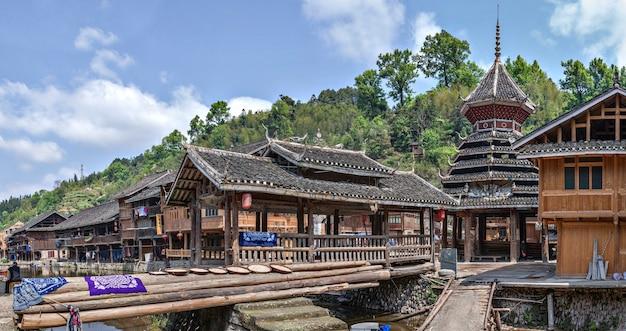 Wioska zhaoxing dong, prowincja guizhou, chiny panoramiczny widok na wioskę mniejszości etniczne, drewniany zadaszony most i wieża bębnów obok drewnianych chat w pobliżu wiejskiej rzeki, wiosna.
