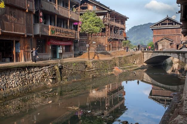 Wioska zhaoxing dong, prowincja guizhou, chiny wiejska rzeka z brukowanym nabrzeżem otoczona drewnianymi chatami, mniejszość wiejska.