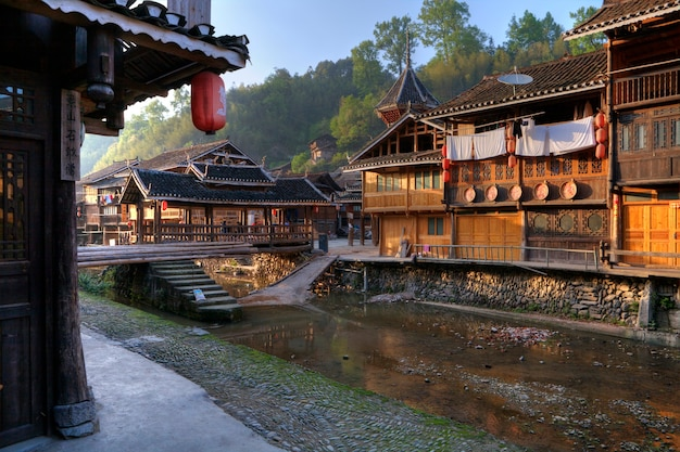 Wioska zhaoxing dong, prowincja guizhou, mniejszości etniczne w południowo-zachodnich chinach w świetle zachodzącego słońca, drewniany dom i zadaszony most nad rzeką wiejską.