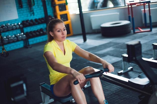 Wioślarstwo na siłowni. młodej kobiety szkolenie używa wioślarską maszynę