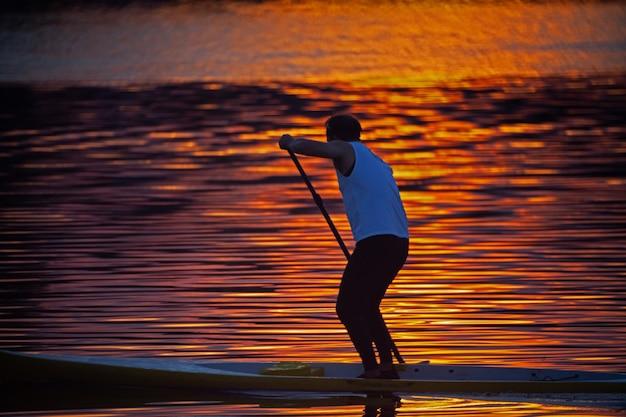 Wioślarze trenują do zwycięstwa wieczorem, podczas niskiego słońca za horyzontem.