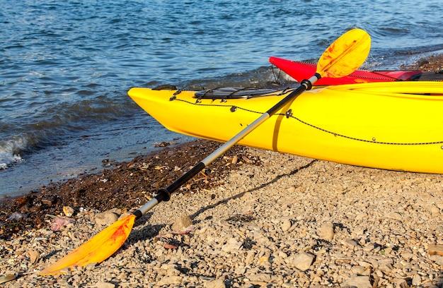 Wiosło do podwójnego żółtego kajaka na brzegu morza na kamczatce