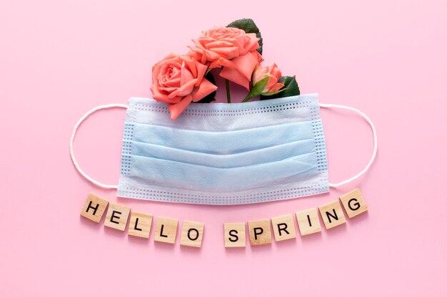 Wiosna 2021. koncepcja covid-19. maska medyczna z wiosennych kwiatów na różowym tle.