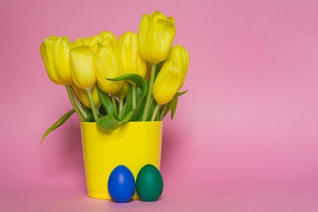 Wiosna bukiet żółtych tulipanów i pisanek malowane na różowym tle. tło wakacje kreatywnych