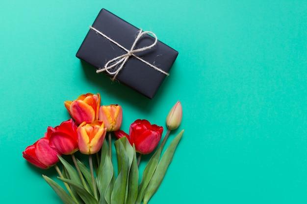 Wiosna kartkę z życzeniami z tulipanami i prezent na zielonej ścianie
