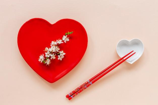 Wiosna kwiatowy japońskie jedzenie koncepcja z kwitnących gałęzi wiśni i porcja z czerwonym naczyniu w kształcie serca