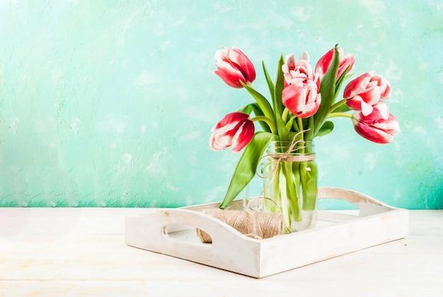 Wiosna kwiaty tulipany w szklanym słoiku z kamienia, na jasnoniebieskim i drewnianym białym.