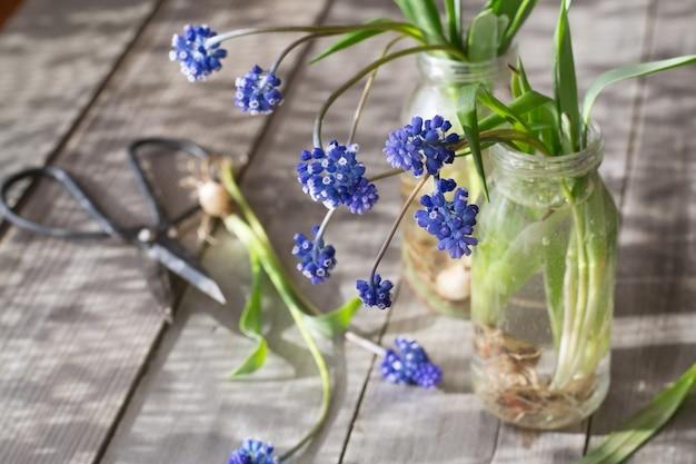 Wiosna kwitnie w butelkach na drewnianym stole