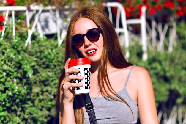 Wiosna lato pozytywny portret młodej hipster dziewczyny, ubrana w codzienny strój w stylu ulicznym, spacerująca po centrum miasta z filiżanką kawy na wynos, niesamowite naturalne imbirowe długie włosy, smaczny napój.