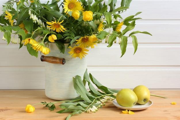 Wiosną martwa natura z kwiatami ogrodowymi i żółtymi jabłkami na stole w stylu rustykalnym.