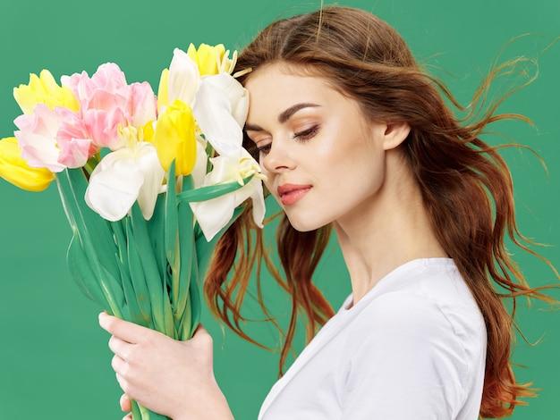 Wiosna młoda piękna dziewczyna z kwiatami na kolorowej powierzchni studia, kobieta pozuje z bukietem kwiatów, dzień kobiet