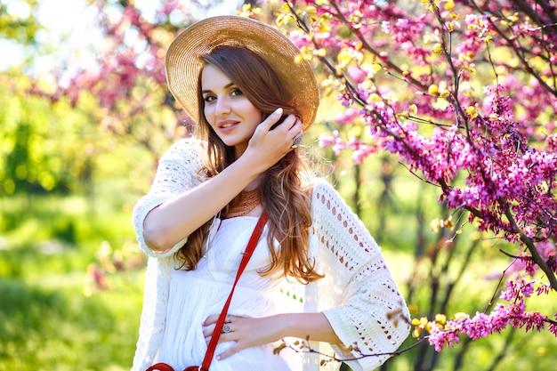 Wiosna moda piękny portret ładna blondynka dama pozuje w kwitnącym ogrodzie, ubrana w biały strój boho i słomkowy kapelusz.