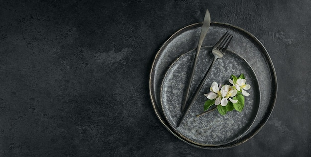 Wiosna nakrycie stołu z kwitnących gałęzi jabłoni i kwiatów na czarnym stole. dekoracja świąteczna w stylu prowansalskim. romantyczna kolacja. narzut z kopią miejsca na tekst