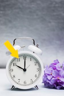 Wiosna ogłasza na zegarze z kwiatami obok