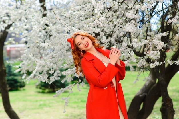 Wiosna piękna dziewczyna z długimi czerwonymi włosami dmuchanie na zewnątrz. kwitnące drzewa. romantyczny portret młodej kobiety. natura