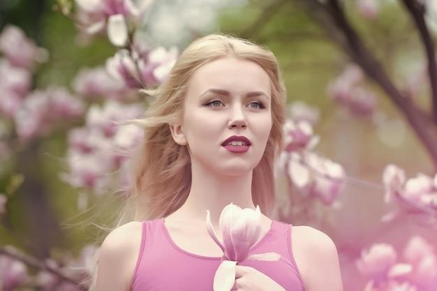 Wiosna, przyroda i środowisko. magnolia kwiat i kobieta w parku kwiat.