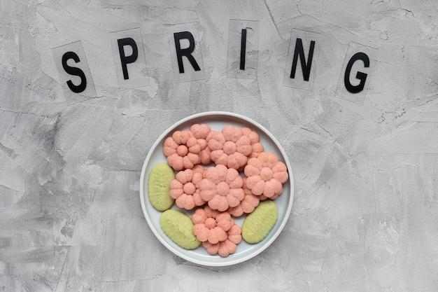 Wiosna słowo i kwiat ciasteczka na talerzu na szarym