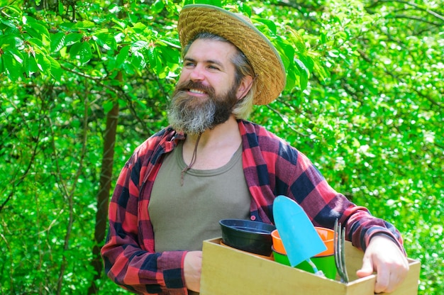 Wiosna. szczęśliwy rolnik w wiosennym ogrodzie. ogrodnik z narzędziami ogrodniczymi.