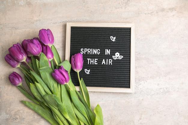 Wiosna w powietrzu na tablicy z literami i bukietem fioletowych tulipanów