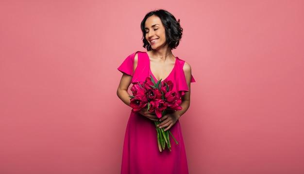 Wiosna. wspaniała kobieta w purpurowej sukience stoi z profilu i trzyma bukiet kwiatów, uśmiechając się z zamkniętymi oczami.
