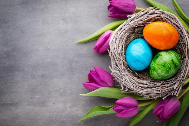 Wiosna z życzeniami. pisanki w gnieździe. wiosenne kwiaty tulipany.