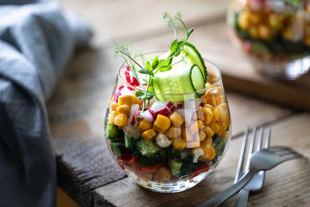Wiosny jarzynowa sałatka w szklanej filiżance na drewnianym tle. odpowiednie odżywianie. skopiuj miejsce pionowy. selektywne ustawianie ostrości.