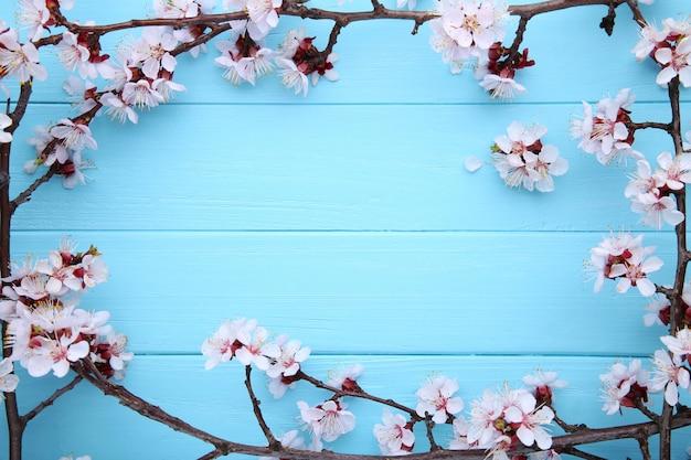 Wiosny kwitnienie rozgałęzia się na błękitnym drewnianym tle z copyspace.