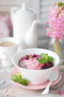 Wiosny śniadanie z filiżanką kawy na drewnianym tle. granola z truskawkami, orzechami i mlekiem.
