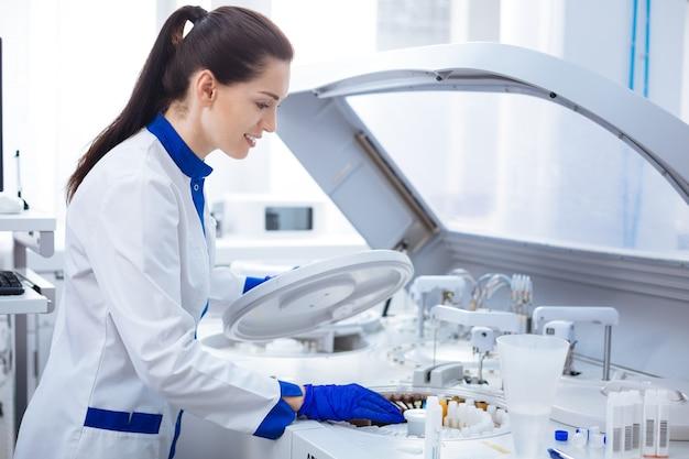 Wirówka. nowa energiczna pracownica laboratoryjna ładuje wirówkę, umieszczając tam próbki i przytrzymując pokrywkę