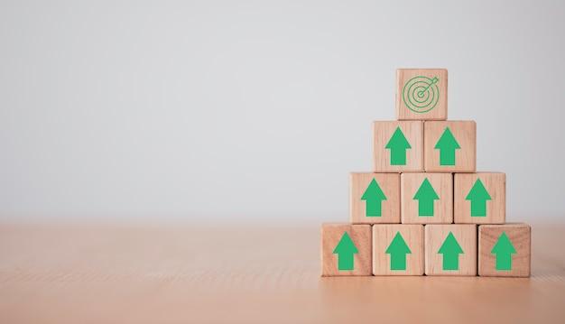 Wirtualna tablica docelowa i strzałka, które drukują ekran na drewnianej kostce cel osiągnięcia biznesowego i koncepcja celu celu.