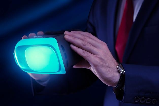 Wirtualne okulary w rękach człowieka biznesu na ciemnym tle z bliska.
