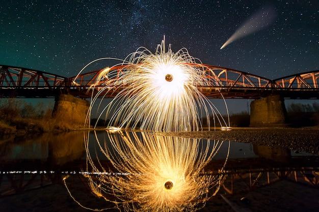 Wirująca stalowa wełna w abstrakcyjnym kręgu, deszcz fajerwerków jasnożółtych iskier na długim moście odbijający się w wodzie rzeki pod rozgwieżdżonym niebem.