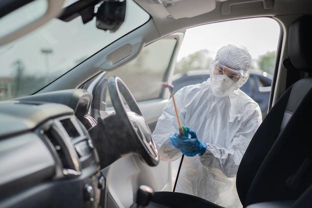 Wirusolodzy noszący zestawy ppe czyszczą wirusa w samochodach.