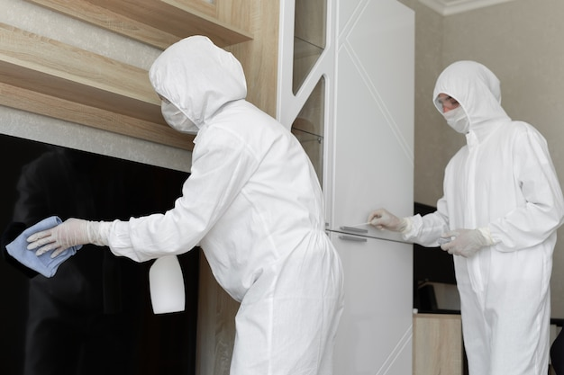 Wirusolodzy, osoby w kombinezonach ochronnych przeprowadzają dezynfekcję