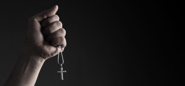 Wisiorek krucyfiks lub znak krzyża wykonany ze srebra i trzymany w dłoni mężczyzny symbolizuje modlitwę za kogoś