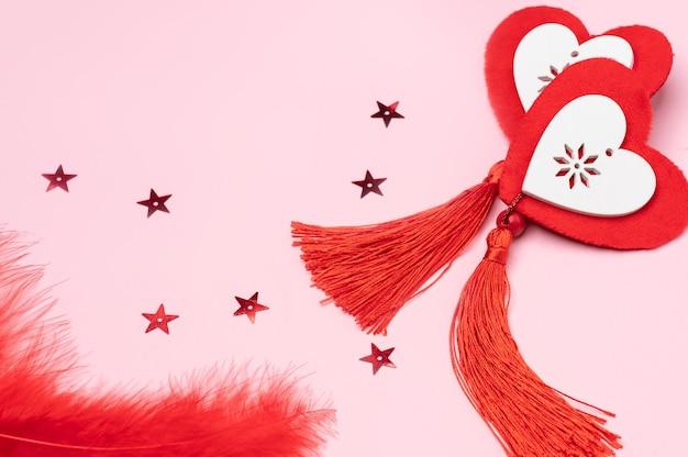 Wisiorki w formie serduszek na różowym tle ozdobione ozdobnymi gwiazdkami i piórkami w stylu walentynkowym