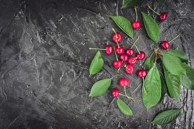 Wiśnia w białym kubku z zielonymi liśćmi na ciemnym drewnie